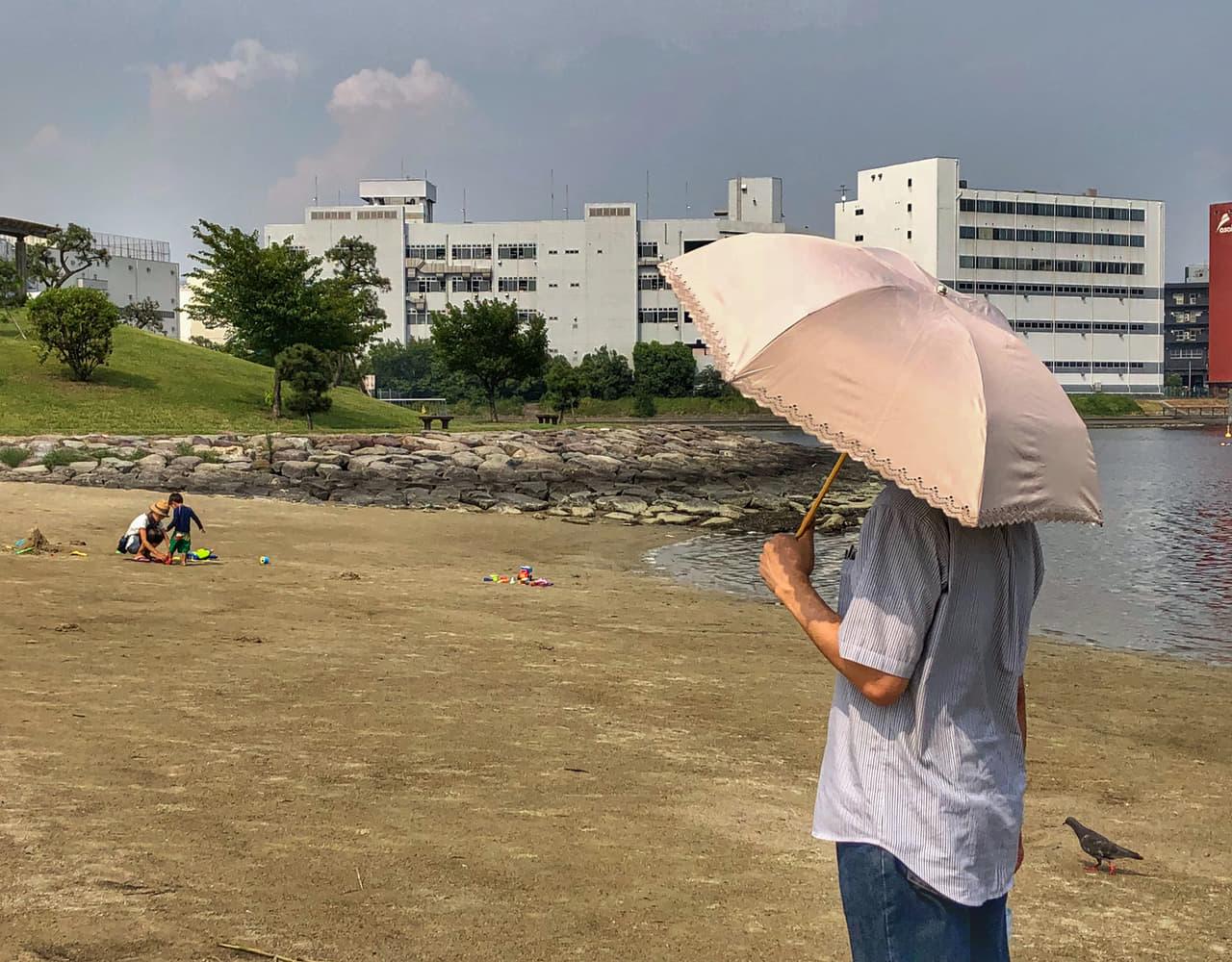 折りたたみ傘を持つ男性