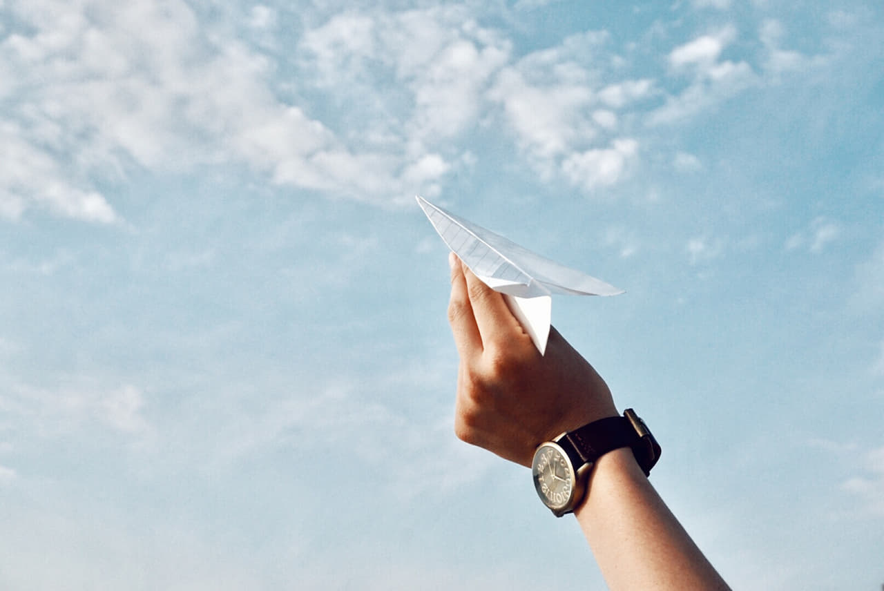 紙飛行機を飛ばす腕時計を付けた手
