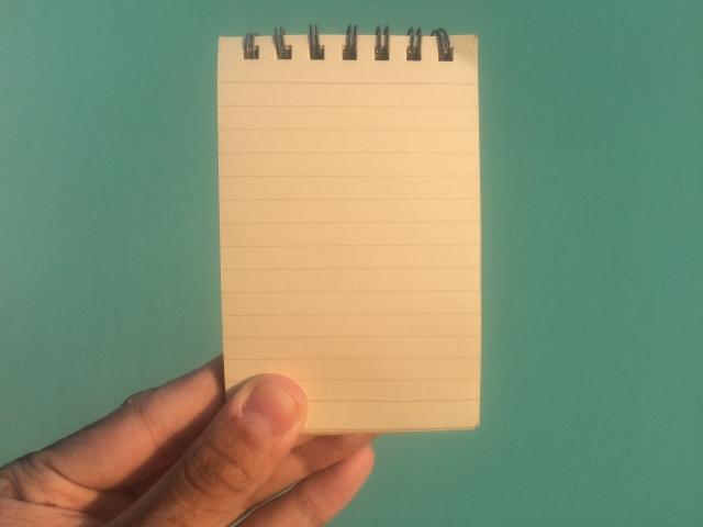メモ帳を持つ手