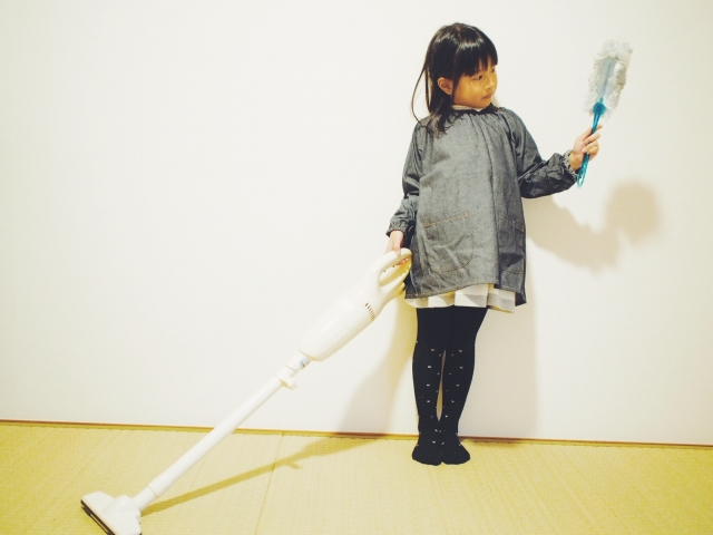スティッククリーナーで掃除する女の子