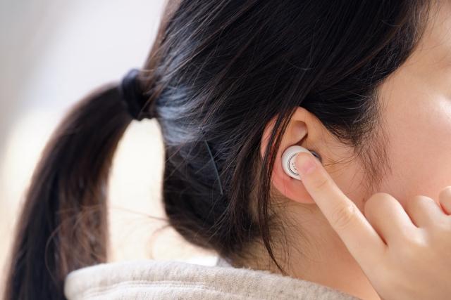 ワイヤレスで音楽を聴く女性