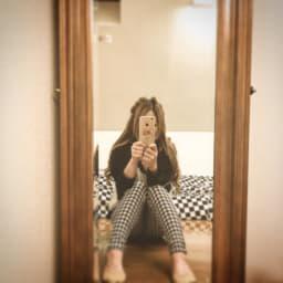 鏡で撮影する女性