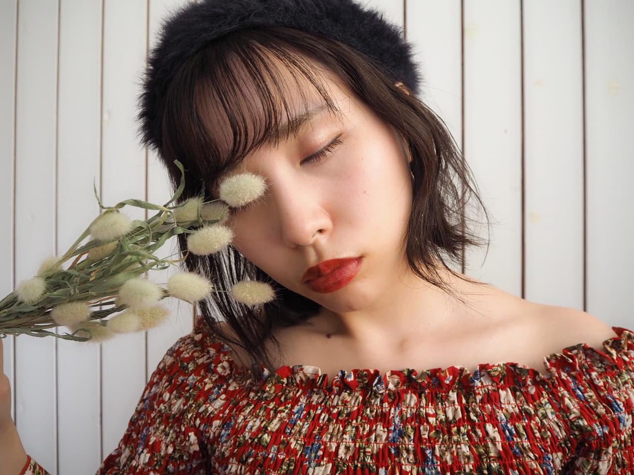 目を閉じた女性と花
