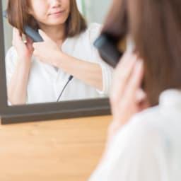 コテで髪を巻く女性の画像
