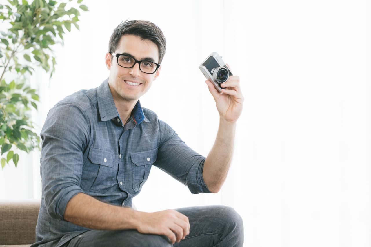 カメラを持って笑う男性の画像