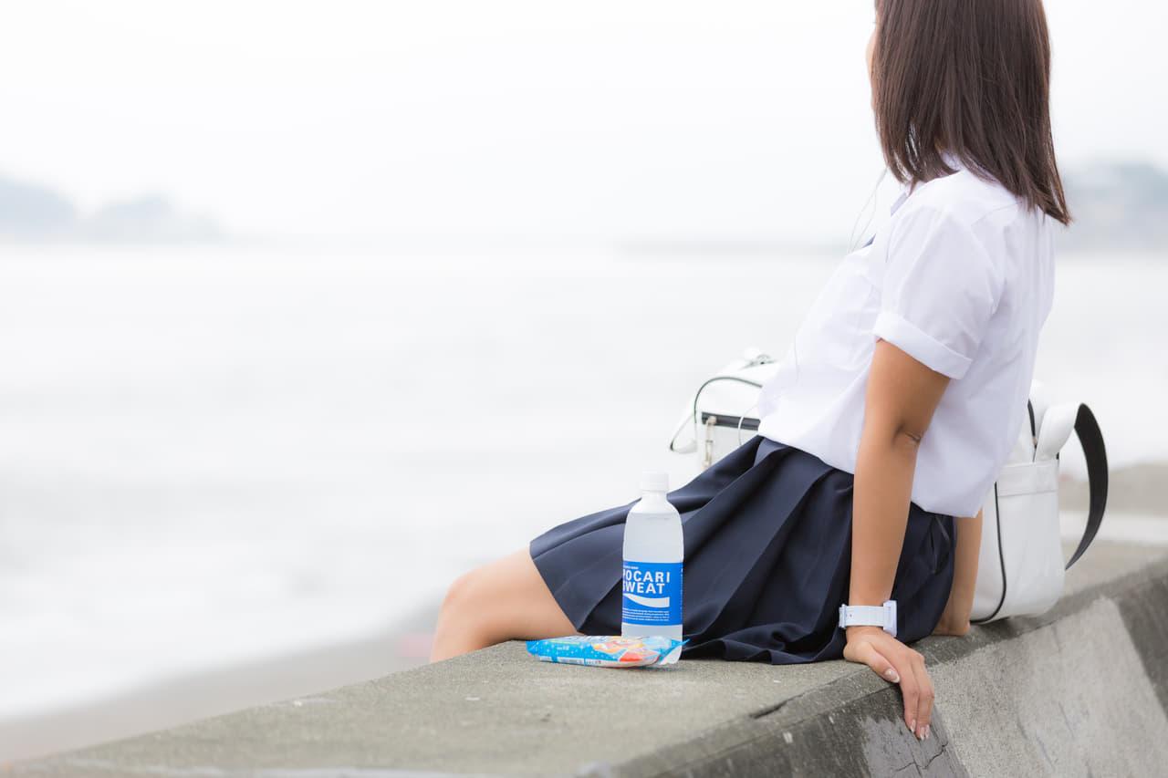 堤防に座る女子高生