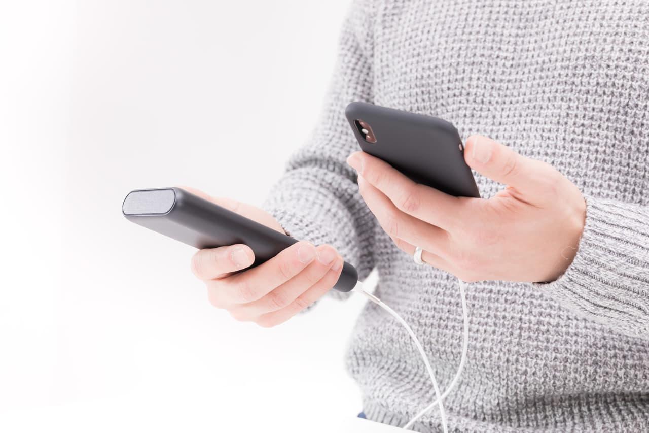 モバイルバッテリーとスマートフォンを持つ男性の画像