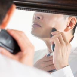 スール姿の髭を剃る男性