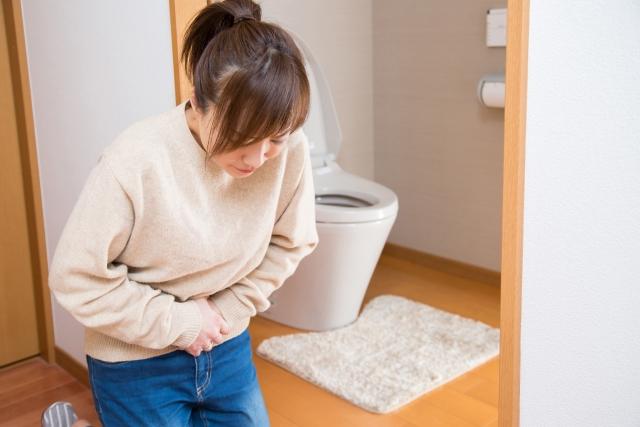 トイレの前でお腹を抑える女性