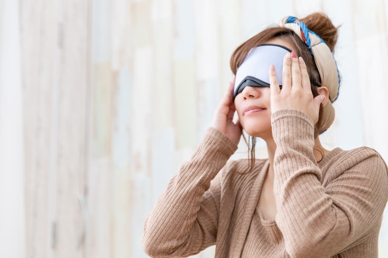 アイマスクをする女性の画像
