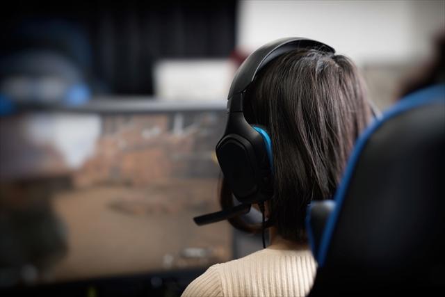 ヘッドホンでPCゲームをする女性