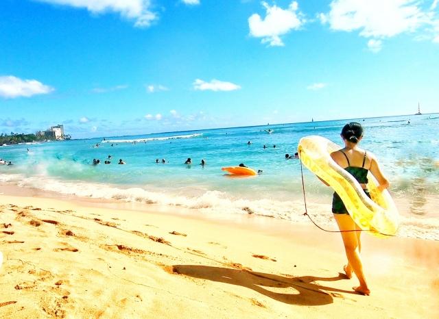 海辺を歩く女性の後ろ姿